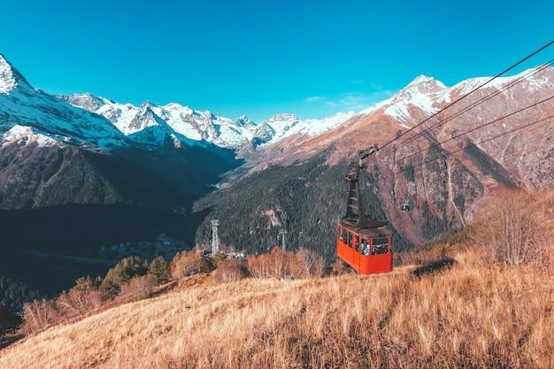 La funivia retrò rossa porta i turisti in cima sullo sfondo delle montagne del caucaso