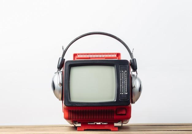 Rosso retrò vecchio portatile mini televisore con le cuffie su sfondo bianco.