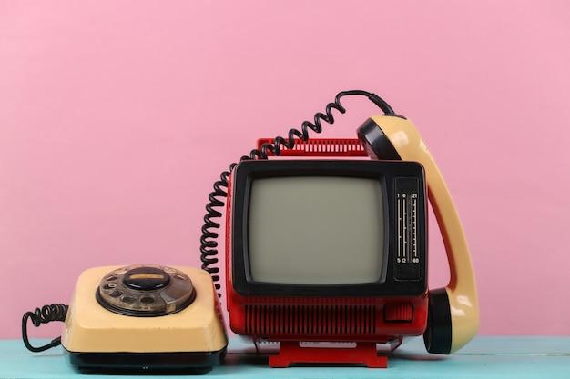 Rosso retrò vecchio portatile mini televisore con telefono rotativo su sfondo rosa.
