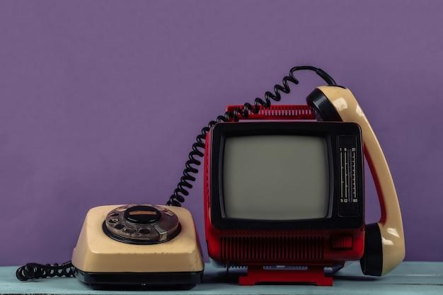Rosso retrò vecchio portatile mini televisore con telefono rotativo su sfondo viola.