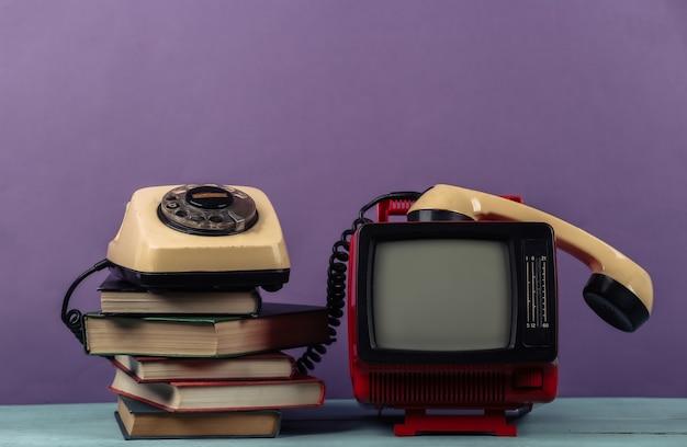 Rosso retrò vecchio portatile mini televisore con telefono rotante, pila di libri su sfondo viola.