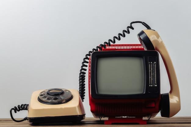 Rosso retrò vecchio portatile mini televisore con telefono rotativo su sfondo bianco.