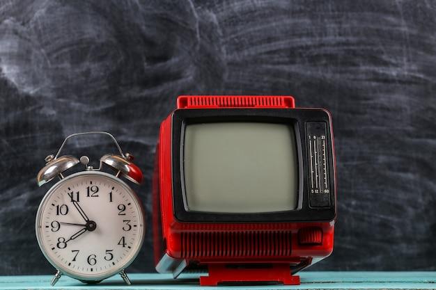 Mini tv portatile retrò vecchia scuola rossa con sveglia su sfondo lavagna