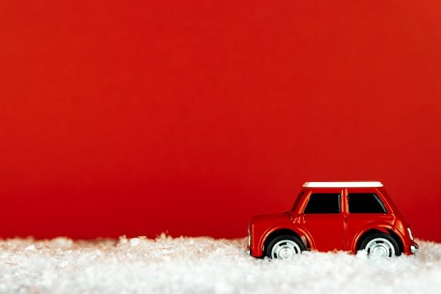 Auto giocattolo retrò rossa su una strada innevata sulla stanza rossa