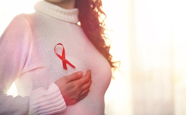 Il nastro rosso della ragazza. la ragazza tiene in mano un nastro rosso. nastro rosso di concetto di salute. tumore al seno.