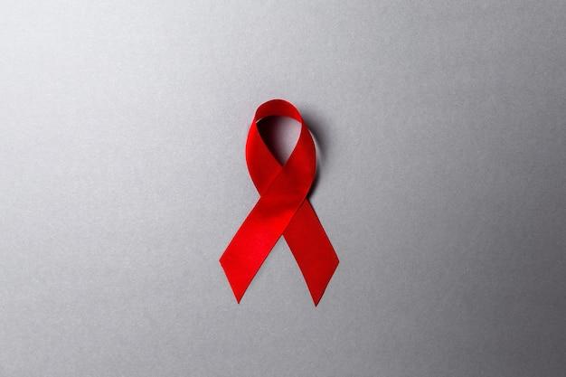 Nastro rosso su sfondo grigio. copia spazio. lay piatto. il concetto di giornata mondiale contro l'aids.