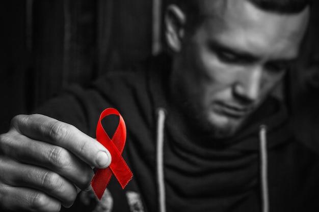 Nastro rosso in mano, simbolo della lotta contro l'hiv, l'aids. concetto di aiutare chi ha bisogno. in bianco e nero.