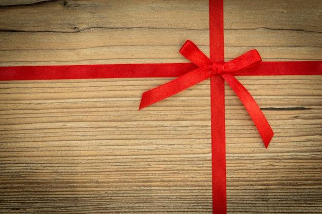 Nastro rosso con fiocco su fondo di legno marrone