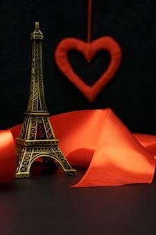 Il nastro rosso avvolge la statuetta della torre eiffel su uno sfondo nero.