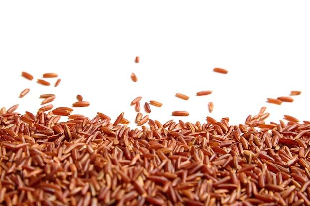 Riso rosso sparsi su sfondo bianco. mucchio di chicchi di riso secchi crudi