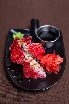 Riso rosso con pesce, wasabi e zenzero su un piatto nero.