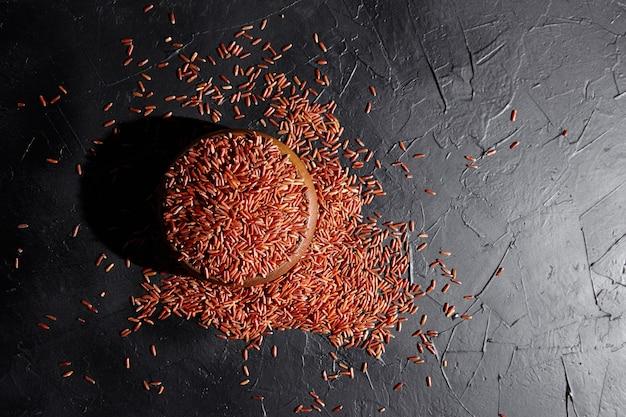 Riso rosso in una ciotola di legno sulla tavola di pietra nera, vista dall'alto. grani crudi secchi