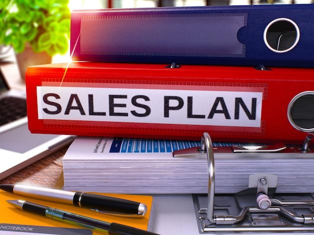 Raccoglitore ad anelli rosso con iscrizione piano di vendita sullo sfondo del tavolo di lavoro con forniture per ufficio e laptop. piano di vendita business concept su sfondo sfocato. rendering 3d.