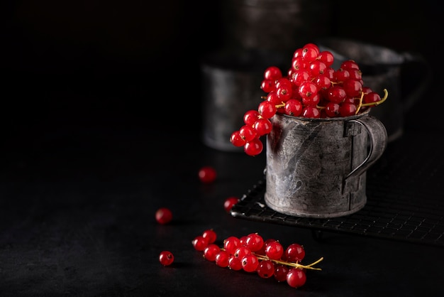Mazzi rossi maturi di ribes in una tazza di ferro su sfondo nero