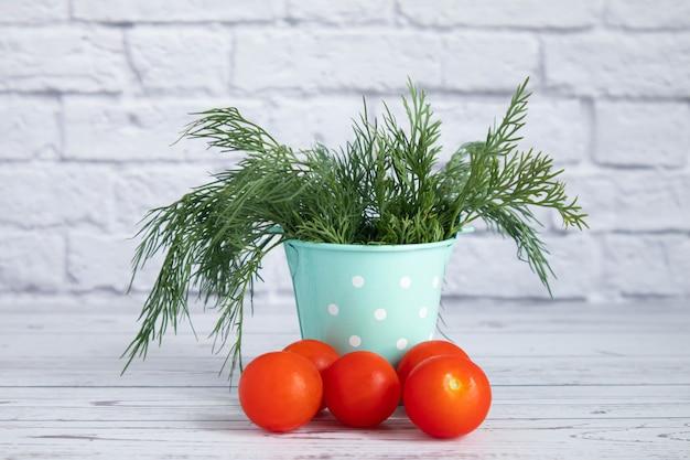 I pomodorini rossi maturi si trovano accanto a un secchio di peltro color menta