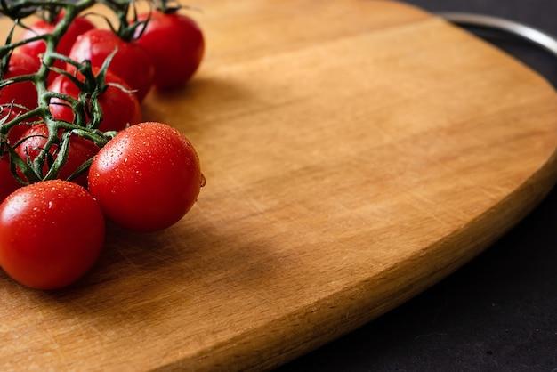 Pomodorini freschi maturi rossi sul ramo sul tagliere di legno