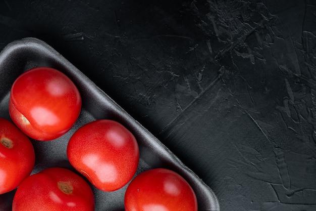 Pomodori rossi maturi, su sfondo nero con copia spazio per il testo