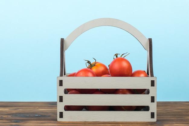 Pomodori maturi rossi in una scatola su un tavolo di legno.