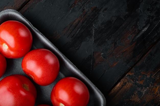 Pomodori maturi rossi, sulla tavola di legno scuro