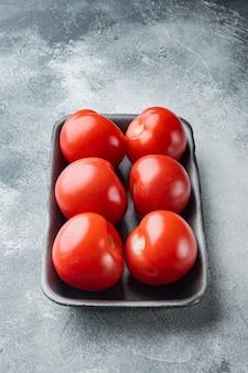 Pomodori maturi rossi, su grigio