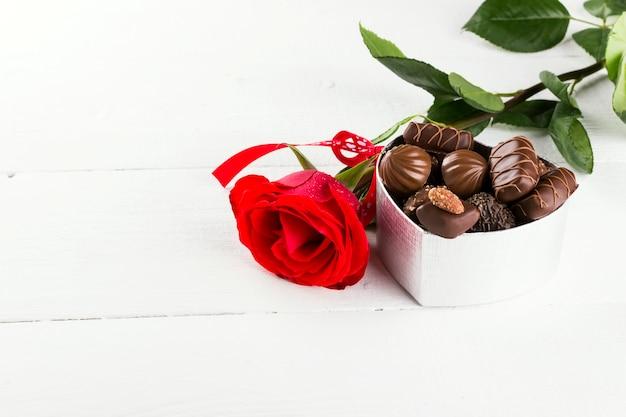 Rosa rossa, scatola di cioccolatini su un fondo di legno bianco