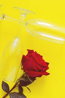 Un fiore di rosa rossa e due bicchieri di vino giacciono su uno sfondo giallo foto verticale vista dall'alto piatta c...