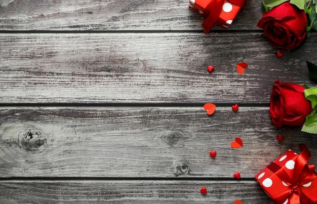 Rosa rossa, confezione regalo e cuore su sfondo di legno con copia spazio per il testo. vista dall'alto il giorno di san valentino concetto.