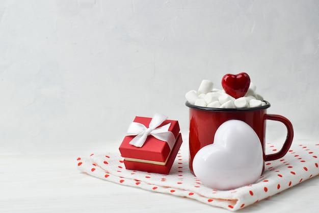 Una rosa rossa con un regalo e una tazza di metallo rossa. biglietto di auguri di san valentino.