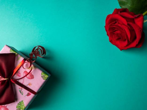 Rosa rossa con petali verdi che si trova su un lato e un grande regalo rosa con un nastro rosso sul verde