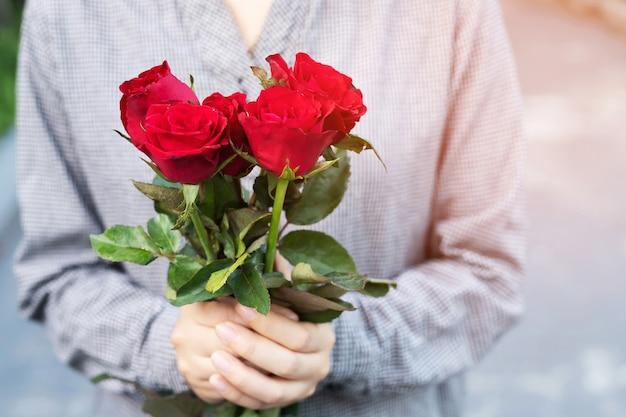 Bouquet di rose rosse nelle mani di womans