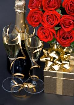 Rose rosse e champagne su sfondo nero. decorazione festiva. disposizione romantica. messa a fuoco selettiva