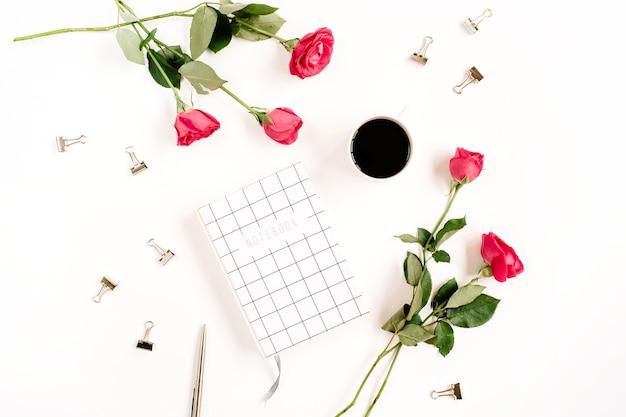 Fiori di rose rosse, tazza di caffè, taccuino e clip su superficie bianca