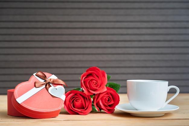 Rose rosse e confezione regalo con tazza di caffè sulla tavola di legno