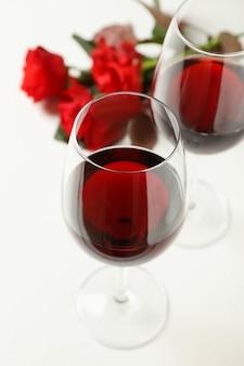 Rose rosse e bicchieri di vino su sfondo bianco