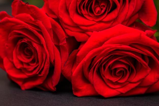 Rose rosse e cuori su sfondo nero. sfondo di san valentino