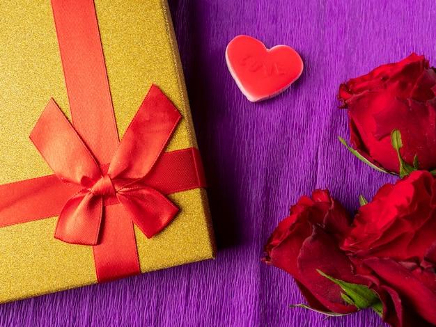 Rose rosse accanto a cuori e regalo giallo con nastro rosso su viola
