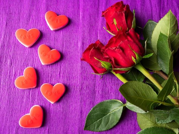 Rose rosse e cuori rossi su viola