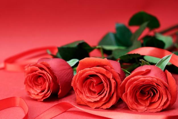 Rose rosse accanto a un nastro rosso, su sfondo rosso. carta di concetto per il giorno di san valentino. copia spazio