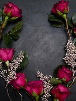 Rose rosse e decorazioni d'argento si mescolano su sfondo scuro. bellissimo design di ghirlande floreali. amore e bellezza. concetto di spazio negativo
