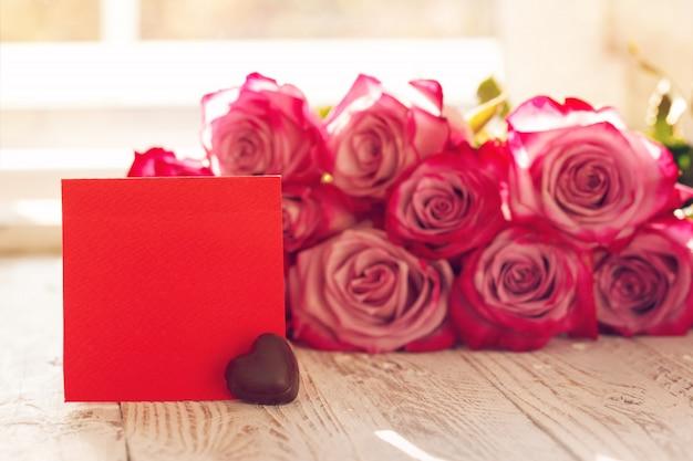 Rose rosse con la cartolina d'auguri rossa in bianco con il cioccolato del cuore per il giorno di biglietti di s. valentino