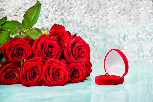 Rose rosse con sfondo boke. scatola con un anello.