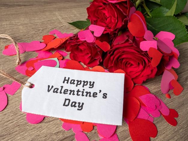 Rose rosse con cuori rosa e rossi nota sul tavolo