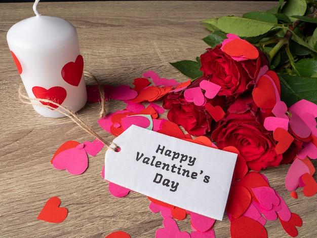 Rose rosse con nota di cuori rosa e rossi e candela bianca sul tavolo