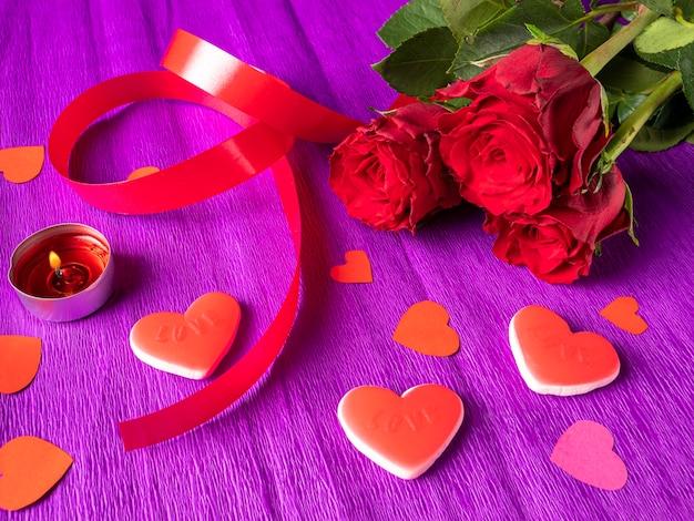 Rose rosse con nastro, cuori e candela accesa su viola