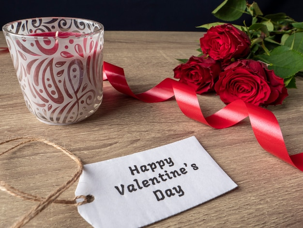 Rose rosse con nastro bianco nota e candela rossa sul tavolo