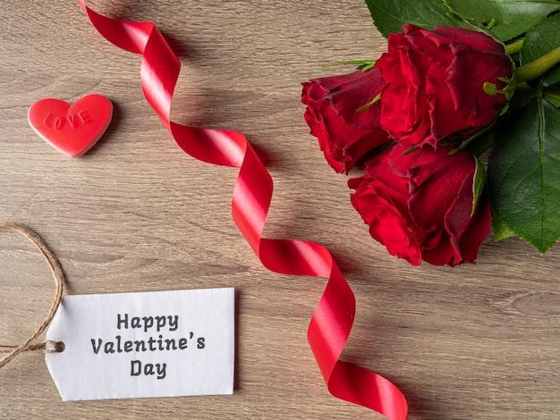 Rose rosse con nastro bianco nota e cuore rosso sul tavolo