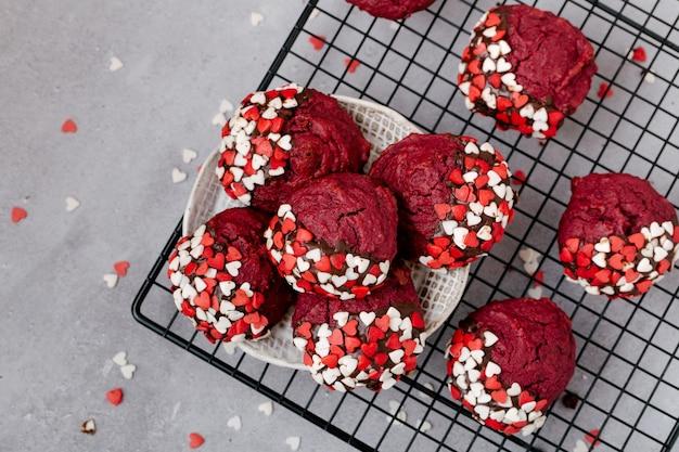 Biscotti rotondi rossi decorati con polvere a forma di cuore per san valentino, su una griglia di metallo nero, sfondo di pietra grigia