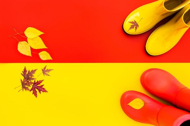 Gli stivali di gomma rossi stanno sul giallo e gli stivali gialli sono sul rosso