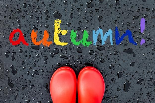 Stivali di gomma rossa su una superficie bagnata coperta di gocce di pioggia e parola arcobaleno