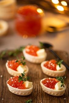 Caviale di salmone salato rosso in tortine di waffle su una tavola di legno, primi piani